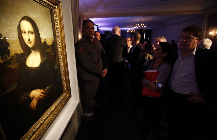 "People look at a painting attributed to Leonardo da Vinci during a presentation in Geneva September 27, 2012. The Mona Lisa Foundation, a non-profit organization, presented historical, comparative and scientific evidence, which demonstrate that there have always been two portraits of the Mona Lisa by Leonardo da Vinci, the ""Earlier Version,"" made 10 years earlier than the ""Joconde"" that is displayed in Le Louvre in Paris. (Denis Balibouse/Reuters)"