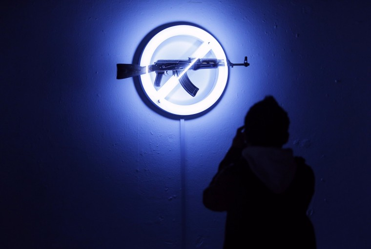 "A visitor looks at Langlands & Bell's ""Sign of the Times"", at the AKA Peace exhibition at the Institute for Contemporary Art (ICA) in central London. Bran Symondson, a former soldier, conceived the AKA Peace project, in which artists turn decommissioned AK47 assault rifles into works of art. (Andrew Winning/Reuters)"