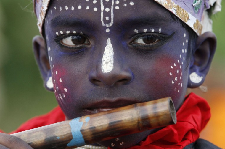 A boy plays a flute as he participates in a fair on the occasion of a traditional boat race on the Kaliganga River in Manikganj. According to the organizers, they are promoting the boat race as an endeavour to uphold the tradition and culture of Bangladesh. Thousands of villagers gather to enjoy a traditional boat race in Kaliganga river of Manikganj district, some 44 km (27 milse) away from Dhaka. (Andrew Biraj/Reuters)