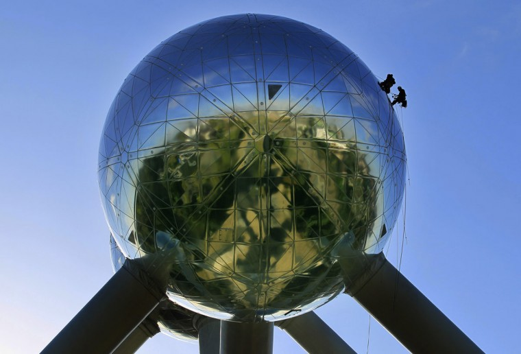 Workers stand on one of the spheres of Brussels' Atomium during a site cleaning. The 102-metre (335 feet) tall structure and its nine spheres symbolise a crystal molecule of metal with its atoms being magnified about 165 billion times. The cleaning of the Atomium, which was designed for the 1958 International Exhibition of Brussels and which received a multimillion-dollar facelift in 2006, will run for a full month. A team of five specialised workers take about three days to clean a ball, each of which has a surface area of 1000 square metres (10,764 square feet). (www.atomium.be/SABAM 2012/Yves Herman/Reuters)