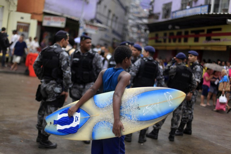 "A boy holds his surf board next to policemen during the inauguration of the Peacekeeping Unit Program (UPP) in Rocinha slum in Rio de Janeiro. The occupation of Rocinha, a notorious hillside ""favela"" that overlooks some of Rio's swankiest areas, is a crucial part of the city's preparations to host soccer's World Cup in 2014 and the Olympics two years later. (Ricardo Moraes/Reuters)"