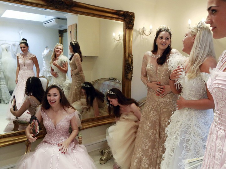 "Debutantes Maria Austin, Amelia Simmons, Sophie Bonello, Zoe Rawson, and Georgina Riddle (L-R) attend a dress-fitting for Queen Charlotte's Ball in central London. Maria, 20, studies drama and theatre studies at Royal Holloway, and would like to either become a classical actor or go into business development. She says she was attracted to take part in the London Season partly because of the work the girls do in charity fundraising. ""A lot of my friends went over to Malawi and Cambodia and did something worthwhile, and I wanted to have the chance to give something back a little bit, so I was really interested in the charity side of it,"" she said. Queen Charlotte's Ball is the crowning event of the London Season, a program for a hand-picked group of girls from rich backgrounds, normally between 17 and 20 years old, involving meetings with aristocracy, etiquette classes, and charity fund-raising. (Olivia Harris/Reuters)"