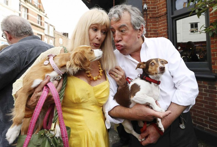Monty Python's Flying Circus actors Terry Jones (R) carries his dog Nancy as he gestures to Talula, the dog of Python actor Carol Cleveland, outside the Angel pub in Highgate, north London. A blue plaque organized by friends and family was unveiled to former Monty Python star Graham Chapman following news that English Heritage had dropped plans for an 'official Blue Plaque to the star, due to budget cuts. Chapman drank, wrote and was barred from the Angel pub in the 1970s. (Olivia Harris /Reuters photo)