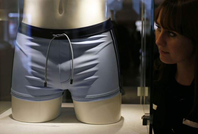 "A employee poses next to a pair of swimming trunks, worn by Daniel Craig in the film ""Casino Royal"", during a media preview of ""50 Years of James Bond - the Auction"", at Christie's in London. The piece is estimated to sell for 2,840 - 4,630 GBP ($4,600-7,500) at auction on October 5. (Stefan Wermuth/Reuters)"