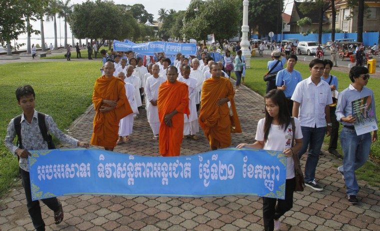 "People and Buddhist monks march during an event commemorating the International Day of Peace near the Royal Palace in Phnom Penh, Cambodia. Banner reads ""Celebrate the intenational day of peace."" (Samrang Pring/Reuters)"
