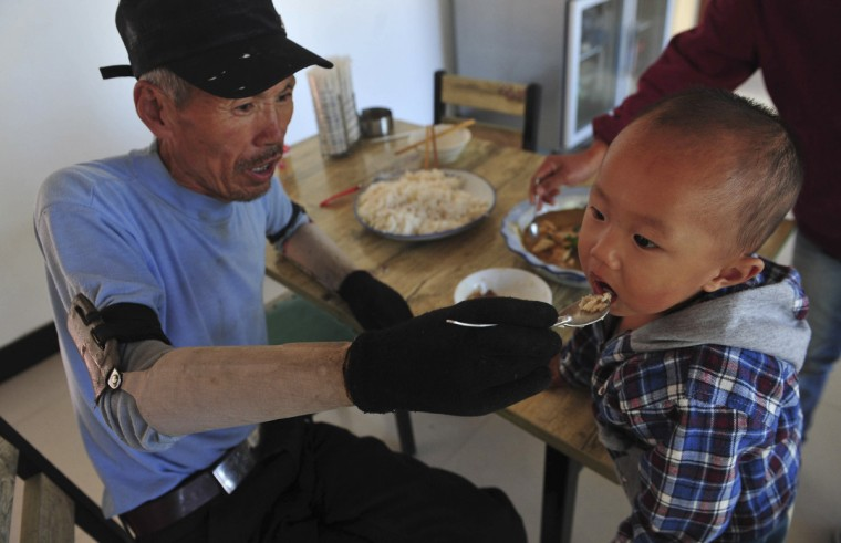 Sun Jifa feeds his grandson during lunch at home in Yong Ji county, Jilin province. Chinese farmer Sun, who lost his forearms in a dynamite fishing accident 32 years ago, could not afford to buy prosthesis. He spent two years guiding his two nephews to build him prosthesis from scrap metal, plastic and rubber. Over the years, Sun and his nephews have built about 300 prosthetic limbs for people in need, charging 3000 RMB ($476) each. (Sheng Li/Reuters)