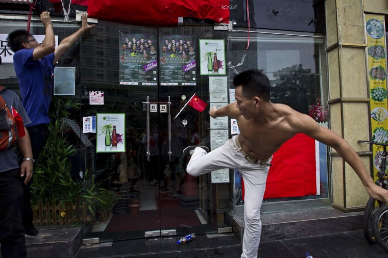 A man kicks the door of a Japanese pub decorated with Chinese national flags during a protest on the 81st anniversary of Japan's invasion of China, in Shenzhen Anti-Japan protests reignited across China on Tuesday, forcing Japanese firms in the country to suspend operations, as a crisis over a territorial dispute escalated on the day Chinese commemorated Japan's 1931 occupation of its giant neighbor. (Keita Van/Reuters)