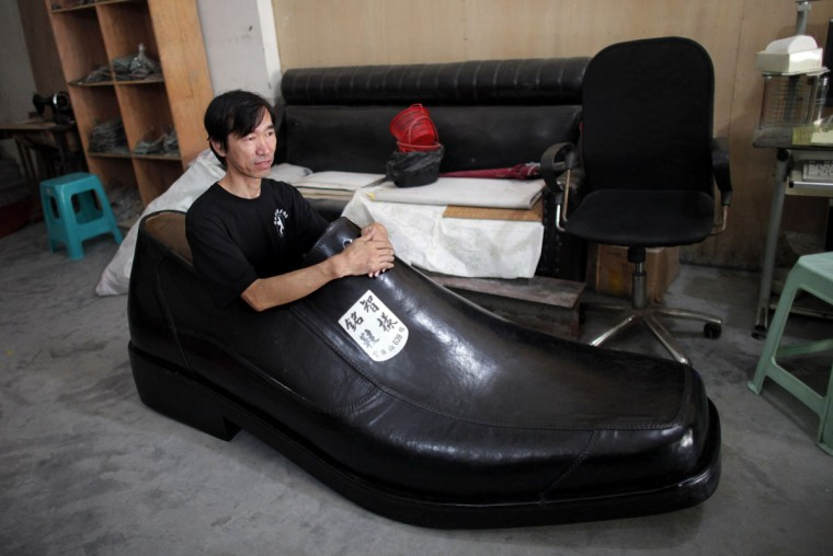Chen Mingzhi, a shoe designer, sits inside of his handmade 6.23 foot-long right shoe at his family store in Wenling, Zhejiang province September 27, 2012. Chen, new to the business of shoe-making, was challenged by a neighbor to create a big shoe. The leather right shoe weighs 83.8 pounds and took him two months to make at a cost of 2,000 rmb ($317.30). (Carlos Barria/Reuters)