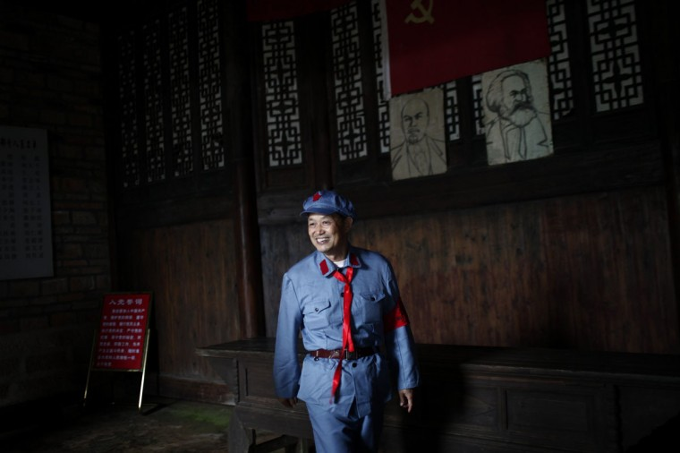A mid-level government official dressed in a red army uniform walks next to portraits of Russian communist revolutionary Vladimir Lenin and German philosopher Karl Marx, as he visits an old house where former Chinese leader Mao Zedong used to live, during a five-day training course at the communist party school called China Executive Leadership Academy of Jinggangshan, in Jiangxi province. (Carlos Barria/Reuters)