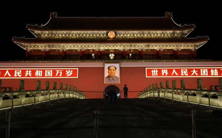 A paramilitary police officer walks in front of a giant portrait of China's late Chairman Mao Zedong at Beijing's Tiananmen Gate, which is decorated to mark the upcoming National Day on October 1, September 27, 2012. (Jason Lee/Reuters)