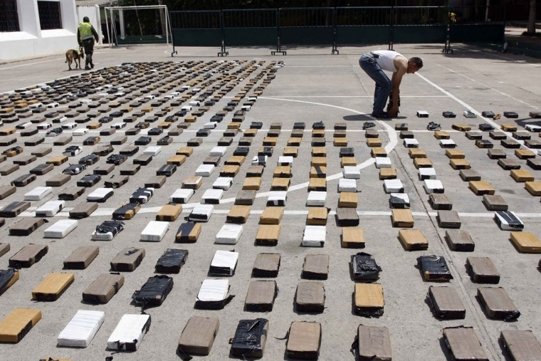 A narcotics police lines up bundles of cocaine, part of a two tons consignment, in Riohacha, Guajira department, September 16, 2012. Authorities seized in various parts of the country around five and a half tons of cocaine in the last three days (Fredy Builes/Reuters)