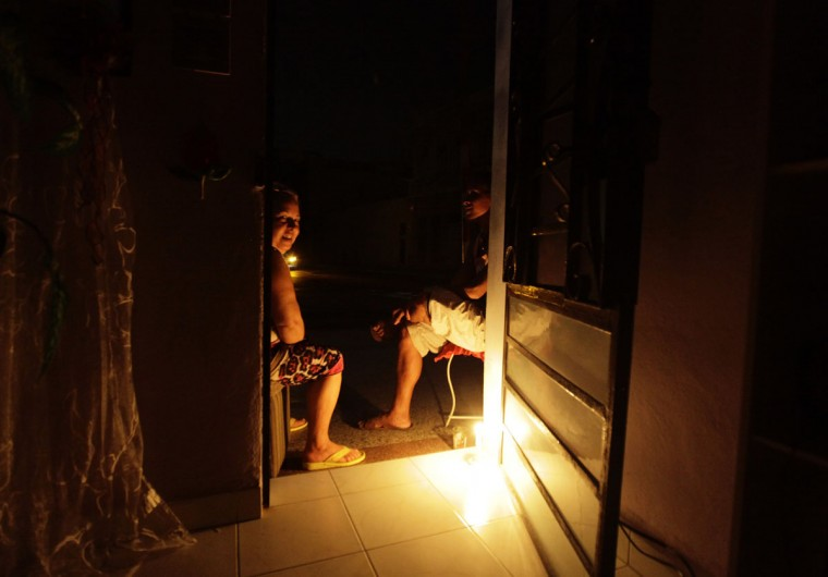 People sit at the doorstep of their home during a power blackout in Havana September 9, 2012. A large swath of Cuba was plunged into darkness on Sunday night in a widespread power failure, the cause of which was not disclosed. (Desmond Boylan/Reuters)