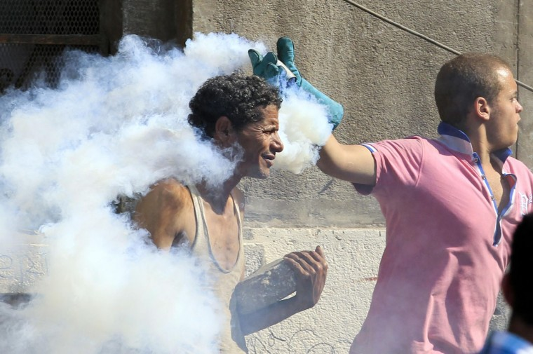 A protester throws a tear gas canister, which was earlier thrown by riot police,and another throws a stone during clashes along a road which leads to the U.S. embassy, near Tahrir Square in Cairo. Egypt's President Mohamed Mursi said on Thursday he supported peaceful protest but not attacks on embassies, after Egyptians angry at a film deemed insulting to the Prophet Mohammad climbed into the U.S. embassy in Cairo and tore down the U.S. flag. He pledged to protect foreigners in Egypt. (Mohamed Abd El Ghany/Reuters)