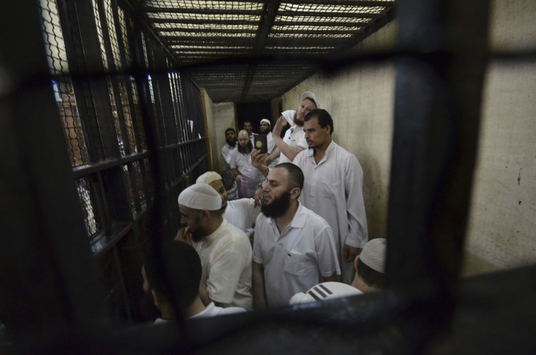 Militant Islamists react during their verdict at a court in Ismailia city, about 75 miles outside of Cairo September 24, 2012. An Egyptian court sentenced on Monday 14 militant Islamists to death by hanging and four to life imprisonment over attacks on army and police forces in the Sinai Peninsula last year. (Stringer/Reuters)