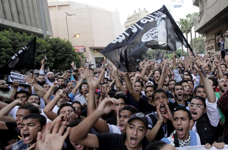 """Egyptian protesters scaled the walls of the U.S. embassy on Tuesday, tore down the American flag and burned it during the protest, and in place of the U.S. flag, the protesters tried to raise a black flag with the words """"There is no God but God, and Mohammad is his messenger,"""" a Reuters witness said. (Mohamed Abd El Ghany/Reuters)"""