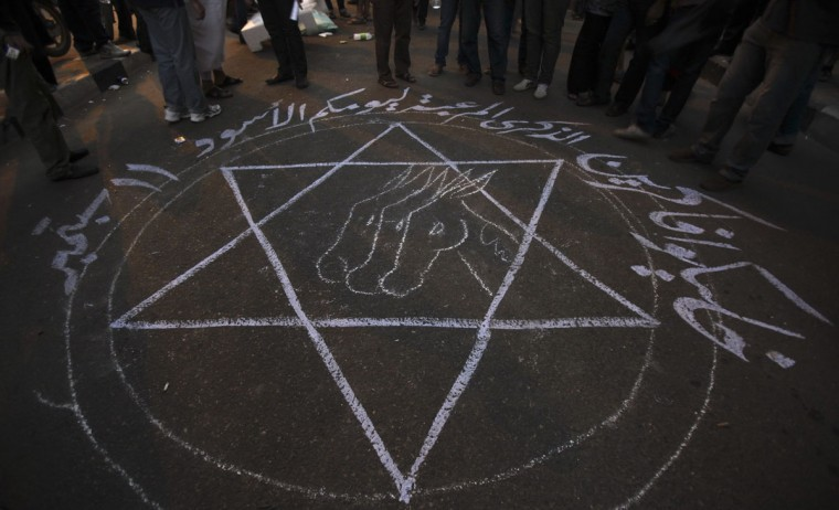"""People stand around a drawing that says """"Remember your black day 11 September"""" during a protest against what they said was a film being produced in the United States that was insulting to the Prophet Mohammad, in front of the U.S. embassy in Cairo September 11, 2012. (Amr Abdallah Dalsh/Reuters)"""