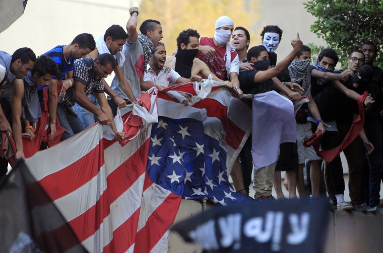 Protesters destroy an American flag pulled down from the U.S. embassy in Cairo September 11, 2012. (Mohamed Abd El Ghany/Reuters)