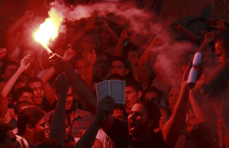 People shout slogans and light flares in front of the U.S. embassy during a protest against what they said was a film being produced in the United States that was insulting to the Prophet Mohammad, in Cairo September 11, 2012. (Amr Abdallah Dalsh/Reuters)