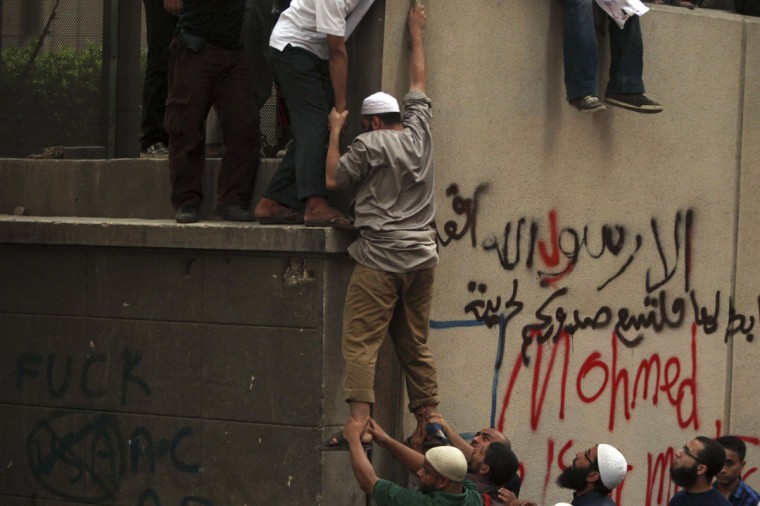 A man climbs the wall of the U.S. embassy during a protest in Cairo September 11, 2012. (Amr Abdallah Dalsh/Reuters)