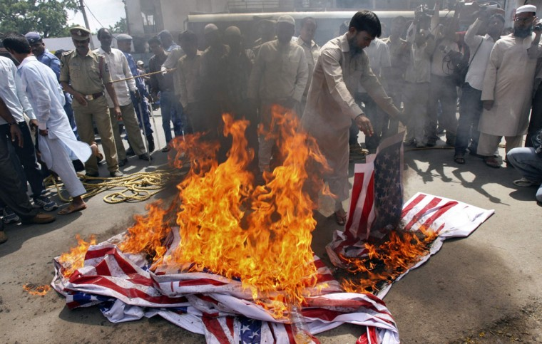 A Muslim man burns a U.S. flag during a protest against a film they consider blasphemous to Islam, outside a mosque in the southern Indian city of Hyderabad. (Krishnendu Halder/Reuters)