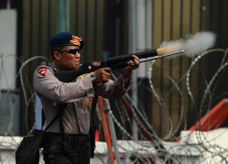 A policeman shoots a tear gas canister towards Indonesian Muslim protesters during a demonstration in front of the U.S. embassy in Jakarta September 17, 2012. (Beawiharta/Reuters)