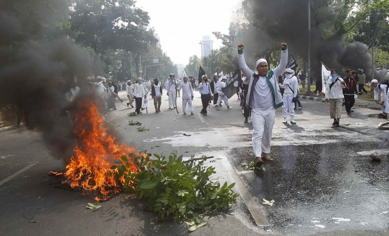 """Muslim protesters shout """"God is Great"""" during a clash with police in front of the U.S. embassy in Jakarta September 17, 2012. (Supri/Reuters)"""