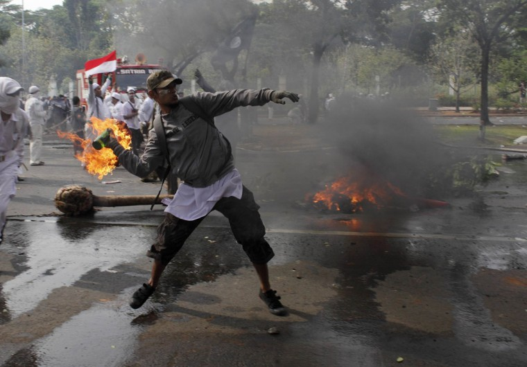 An Indonesian Muslim protester throws a Molotov cocktail towards the police during a protest in front of the U.S. embassy in Jakarta September 17, 2012. Indonesia police used teargas and water cannon on Monday to disperse hundreds of demonstrators who massed outside the U.S. embassy in Jakarta to protest against a film mocking the Prophet Mohammad. (Beawiharta/Reuters)