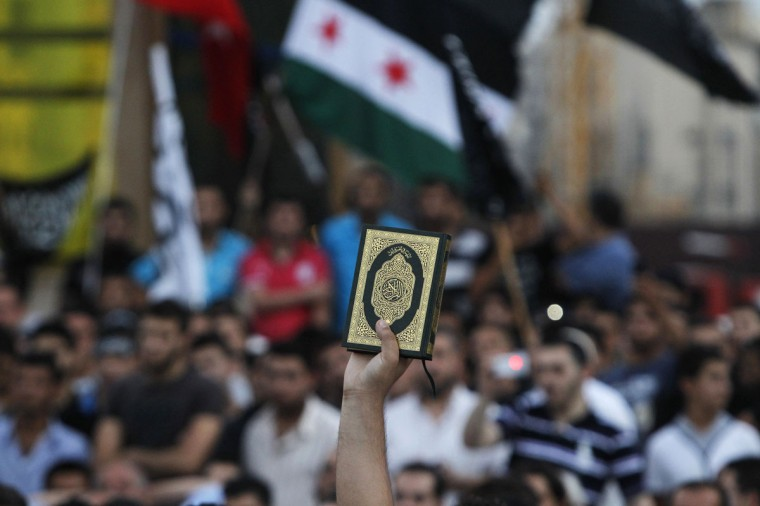 A supporter of Sunni Muslim Salafist leader Ahmad al-Assir holds up a copy of the Koran as others wave Syrian opposition and Islamic flags at a protest against an anti-Islam film made in the U.S. that mocks the Prophet Mohammad, at Martyrs' square in downtown Beirut. (Mohamed Azakir/Reuters)
