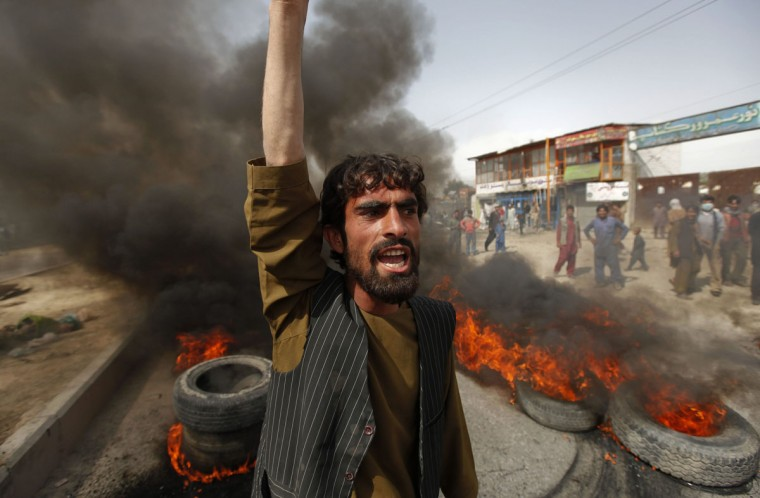 An Afghan protester shouts slogans near burning tyres during a demonstration in Kabul September 17, 2012. (Omar Sobhani/Reuters)