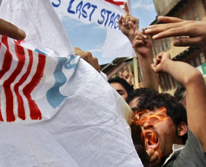 A Kashmiri Muslim protester shouts slogans in front a burning American and Israeli flag, that have been joint together, during a strike in Srinagar September 18, 2012. (Fayaz Kabli/Reuters)