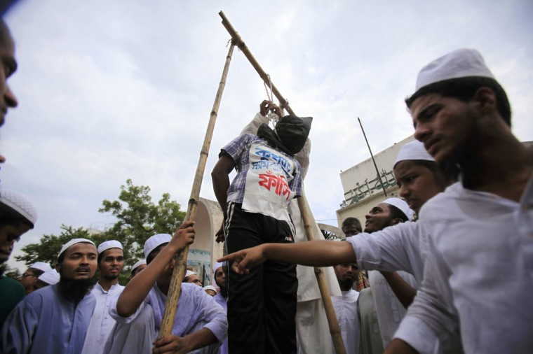 "Bangladeshi Muslims perform a mock execution of the filmmaker of an anti-Islam film made in the U.S. during a protest in front of the National Mosque in Dhaka. The word on the shirt reads, ""Execution."" (Andrew Biraj/Reuters)"
