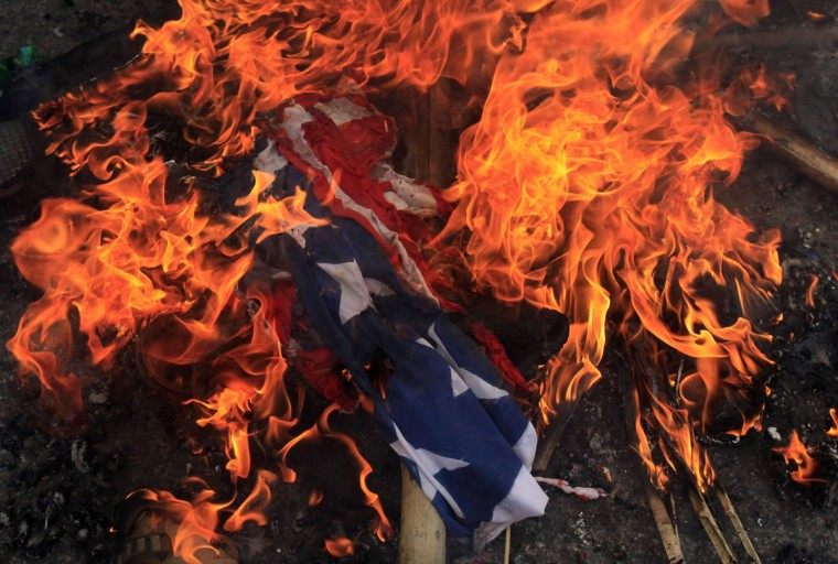A burning U.S. flag is seen on the ground after it was set on fire by Bangladeshi Muslims during a protest in front of the National Press Club in Dhaka. About 10,000 Bangladeshi Muslims participated in demonstrations after Friday prayers in Bangladesh's capital against an anti-Islam film made in the U.S. and also against cartoons mocking the Prophet Mohammad published on Wednesday in a French magazine. (Andrew Biraj/Reuters)