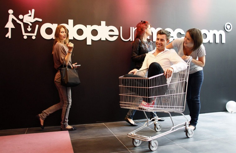 """A single woman pushes a bachelor riding in a shopping trolley at the """"adopt-a-guy"""" (adopte-un-mec) store in Paris September 12, 2012. The boutique, with a short-term lease which expires at the end of the week, opened its doors on Tuesday, promising a high-end shopping experience for women searching for Mr Right. (Jacky Naegelen/Reuters photo)"""