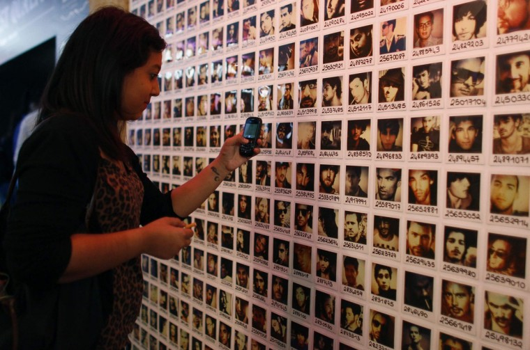 "A single woman looks at photos of bachelors which are on display at the French dating site ""adopt-a-guy"" (adopte-un-mec) store in Paris September 12, 2012. The boutique, with a short-term lease, opened its doors on Tuesday, promising a high-end shopping experience for women searching for Mr Right. (Jacky Naegelen/Reuters photo)"