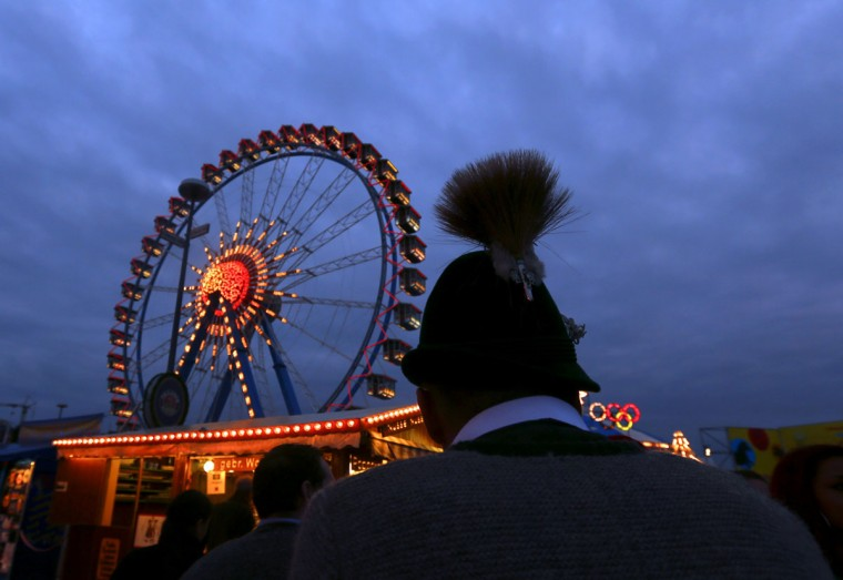 A visitor wearing a traditional Bavarian hat stands in front of a ferris wheel at the Oktoberfest fairgrounds in Munich, Germany. (Michael Dalder/Reuters)