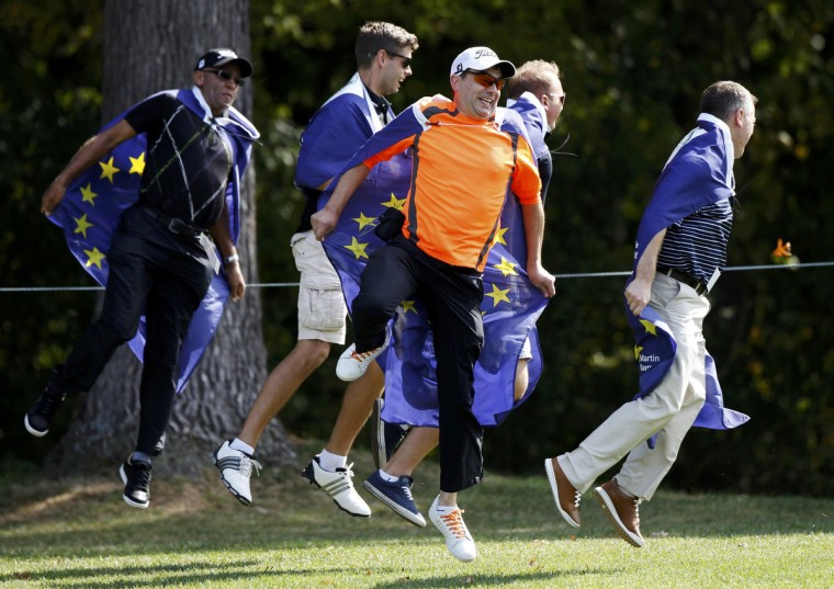 A group of Team Europe fans jump in the air after running along a fairway during a practice round at the 39th Ryder Cup matches at the Medinah Country Club in Medinah, Illinois. (Jeff Haynes/Reuters)