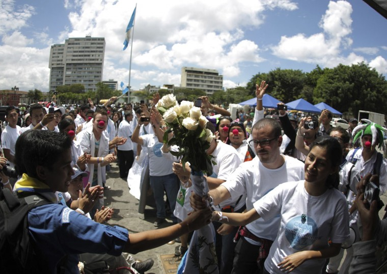 People pass a bouquet of roses along a human chain on the streets of downtown Guatemala city to commemorate International Day of Peace in Guatemala City. (Jorge Dan Lopez/Reuters)