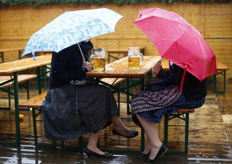 "Revelers sit under umbrellas at a beer garden table with their traditional one-liter ""Masskrug"" beer mugs. (Kai Pfaffenbach/Reuters)"