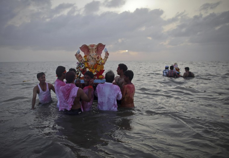 Devotees carry a statue of the Hindu god Ganesh, the deity of prosperity, into the Arabian Sea on the first day of the ten-day-long Ganesh Chaturthi festival in Mumbai. Ganesh idols are taken through the streets in a procession accompanied by dancing and singing and later immersed in a river or the sea symbolizing a ritual seeing-off of his journey towards his abode, taking away with him the misfortunes of all mankind. (Danish Siddiqui/Reuters)