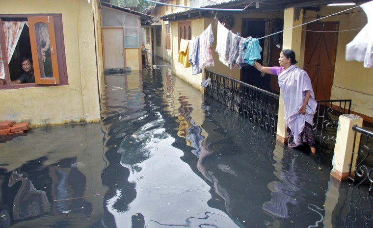 A woman hangs her clothes outside her partially submerged home during flooding in Pandu in the northeastern Indian state of Assam September 24, 2012. Floods and landslides caused by relentless rain in northeast India have killed at least 33 people and displaced more than a million over the past week, officials said on Monday. (Utpal/Reuters)
