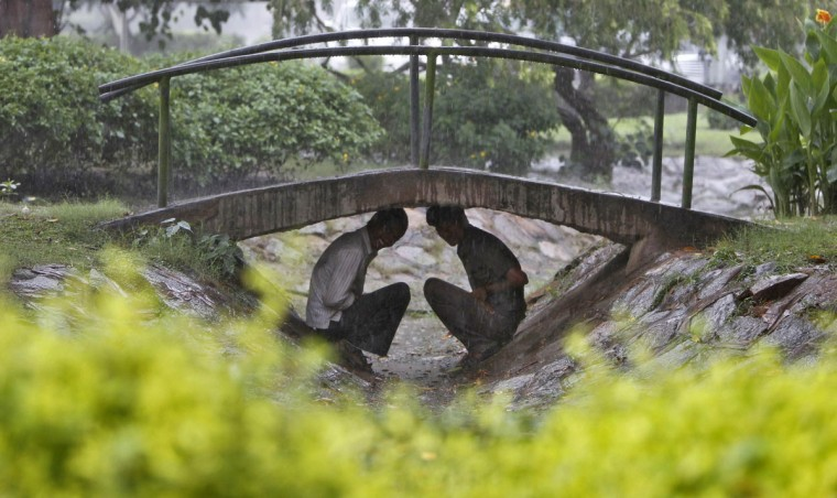 Men take shelter under a footbridge in a park during a rain shower in New Delhi. India's monsoon rains were 31 percent above average in the week to September 5, the weather office said last week, the second straight week of heavier than normal rains, reducing the threat of a prolonged drought in the south Asian country. (Mansi Thapliyal/Reuters)