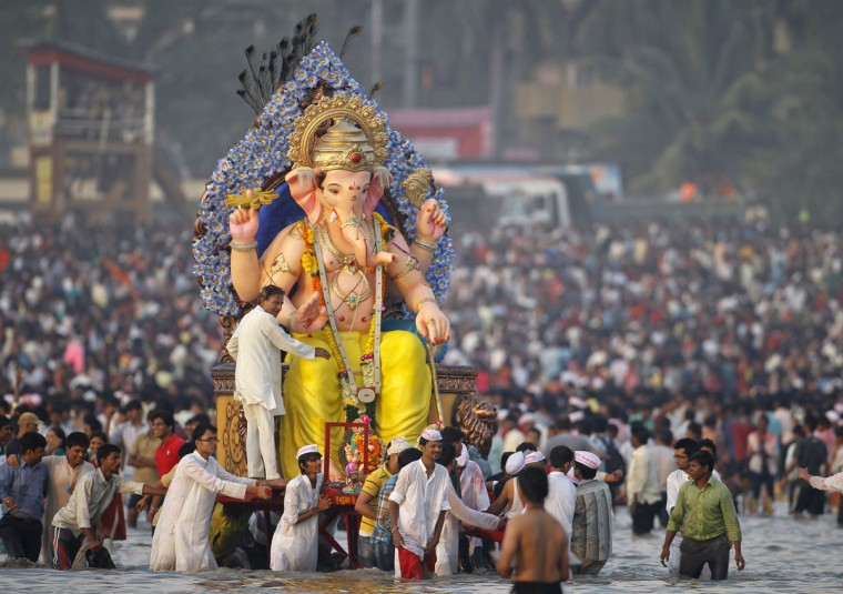Devotees carry an idol of the Hindu elephant god Ganesh for immersion into the Arabian Sea on the last day of the Ganesh Chaturthi festival in Mumbai. Ganesh idols are taken through the streets in a procession accompanied by dancing and singing and later immersed in a river or the sea symbolizing a ritual seeing-off of his journey towards his abode, taking away with him the misfortunes of all mankind. (Vivek Prakash/Reuters)