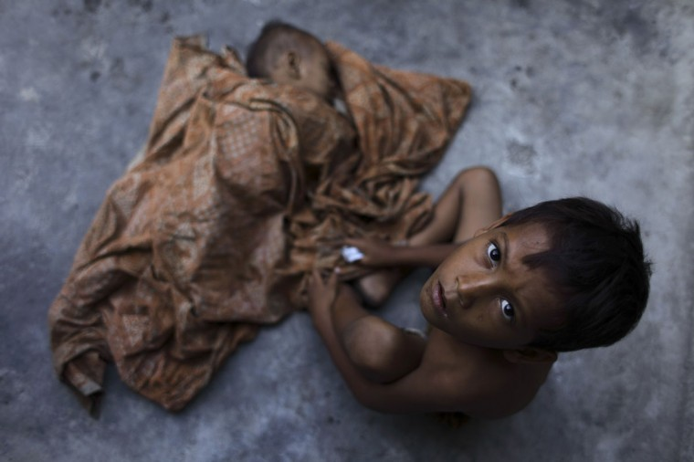 Seven-year-old Mamat (R) sits beside his younger brother who is sleeping on the floor at a slum area in Jakarta. (Beawiharta/Reuters)