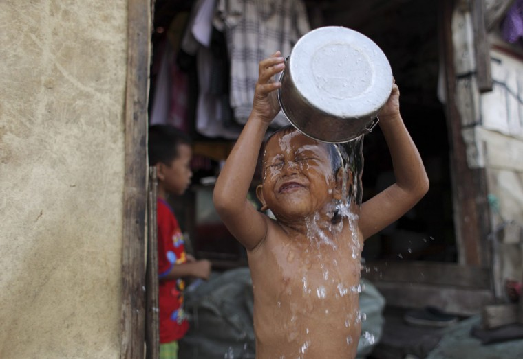 Four-year-old Rizky pours water on himself as he takes a bath in front of his house at a slum area in Jakarta. (Beawiharta/Reuters)