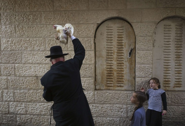 An ultra-Orthodox Jewish man holds a chicken as he performs the Kaparot ritual in Jerusalem's Mea Shearim neighborhood ahead of Yom Kippur, the Jewish Day of Atonement, which starts at sundown on Tuesday. Kaparot is an ancient custom connected to Yom Kippur, where white chickens are slaughtered as a symbolic gesture of atonement. (Ronen Zvulun/Reuters)