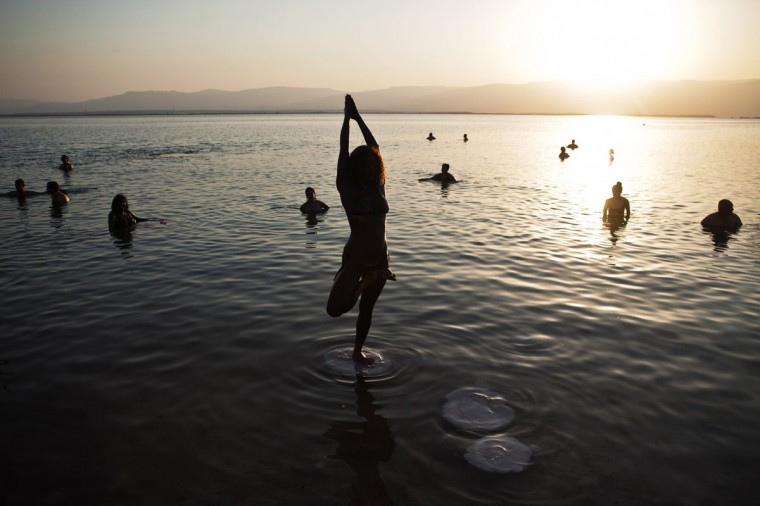 A woman practices yoga during a mass floating event in the Dead Sea. Hundreds took part in the event to raise environmental awareness for the ailing sea, located at the earth's lowest point. The event took place on the one-year anniversary of the day when thousands of naked volunteers posed at the Dead Sea for U.S. artist Spencer Tunick, who also attended Friday's event. (Nir Elias/Reuters)