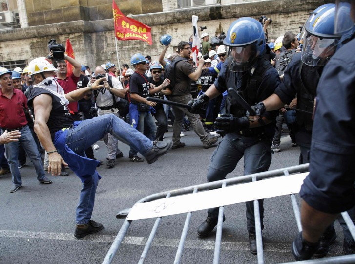 Italian policemen attempt to stop Alcoa Inc's workers as they protest against their dismissals from employment in front of the Ministry of Employment building in Rome September 10, 2012. (Tony Gentile/Reuters)