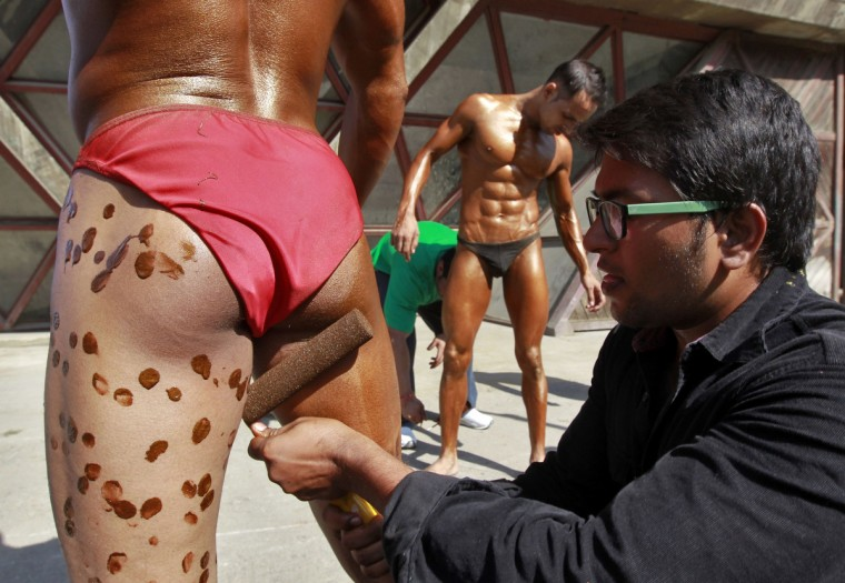 A man applies tanning solution onto a participant backstage before the start of a bodybuilding competition in Srinagar, Pakistan. A total of 70 participants are competing in different bodybuilding categories, organizers said. (Fayaz Kabli/Reuters)
