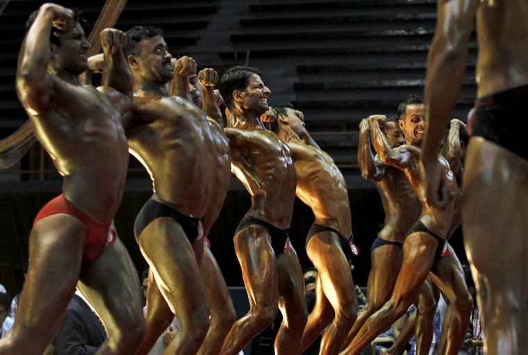 Bodybuilders strike a pose during a bodybuilding competition in Srinagar. A total of 70 participants are competing in different bodybuilding categories, organizers said. (Fayaz Kabli/Reuters)