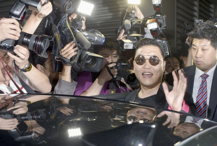 "South Korean singer Psy (front R) arrives from the U.S., at the Incheon International Airport in Incheon, west of Seoul. The pop star whose song ""Gangnam Style"" became the first Korean hit to top Apple's music download charts has also worked his magic on his father's software firm, helping it double in value since singer and dancer Psy burst onto the global scene in July. (Kim Young-Wook/Newsis/Reuters)"